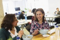 Happy businesswomen eating lunch in office — Stock Photo