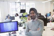 Portrait smiling, confident Indian computer programmer in turban in office — Stock Photo