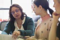 Деловые женщины обсуждают бумажную работу в офисе — стоковое фото