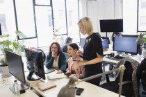 Бізнес-леді працює за комп'ютером в офісі відкритого планування — стокове фото