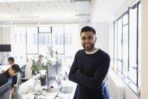 Retrato sorridente, empresário confiante no escritório em plano aberto — Fotografia de Stock