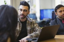 Empresario en el portátil hablando con su colega - foto de stock