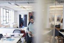 Homme d'affaires indien en turban en utilisant le téléphone intelligent dans le bureau — Photo de stock