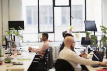 Бизнесмены, работающие в офисе открытой планировки — стоковое фото