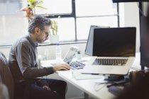 Homme d'affaires concentré travaillant à l'ordinateur portable dans le bureau — Photo de stock