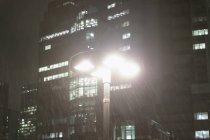 Rain falling around streetlamp below urban highrise buildings at night — Stock Photo