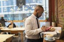 Homme d'affaires utilisant téléphone intelligent et déjeuner dans un café — Photo de stock