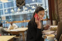 Smiling businesswoman talking on smart phone and working at laptop in cafe — Stock Photo