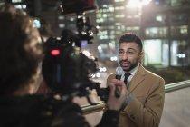 Journaliste et cameraman sur le trottoir urbain — Photo de stock