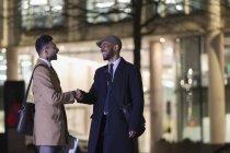 Empresários aperto de mão na rua urbana à noite — Fotografia de Stock