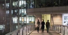 Бізнес людей, що йдуть на міських пішохідний міст уночі — стокове фото
