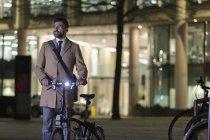 Homem de negócios com a bicicleta na rua urbana à noite — Fotografia de Stock