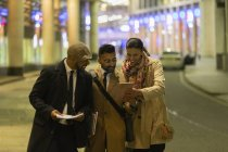 Business people using digital tablet on urban street at night — Stock Photo