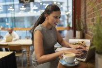 Businesswoman working at laptop in cafe — Stock Photo