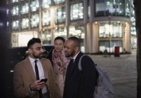 Business people with smart phone talking on city street at night — Stock Photo