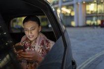 Mujer de negocios usando el teléfono inteligente en taxi de crowdsourced por la noche - foto de stock