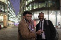 Деловые люди используют смартфон на городской улице ночью — стоковое фото