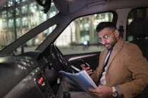 Businessman with smart phone reading paperwork in car at night — Stock Photo