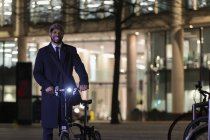 Empresário confiante de retrato com bicicleta na rua urbana à noite — Fotografia de Stock