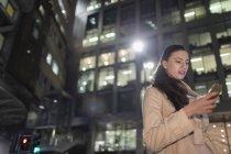 Donna d'affari utilizzando smart phone sotto highrise urbano di notte — Foto stock