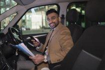Portrait souriant homme d'affaires avec téléphone intelligent lecture de paperasse en voiture dans la nuit — Photo de stock