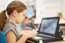 Girl playing game on laptop — Stock Photo