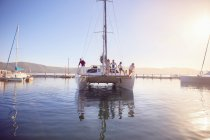 Friends on catamaran in sunny harbor — Stock Photo