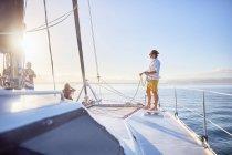Jovem segurando corda de aparelhamento no catamarã ensolarado — Fotografia de Stock
