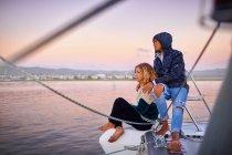 Casal jovem relaxante no barco ao pôr do sol — Fotografia de Stock