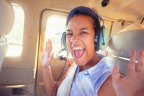 Портрет восторженная молодая женщина с наушниками верхом на самолете — стоковое фото