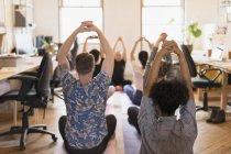 Pessoas de negócios criativas praticando ioga no escritório — Fotografia de Stock