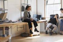 Kreative Geschäftsfrau mit Kopfhörern am Schreibtisch im Büro — Stockfoto