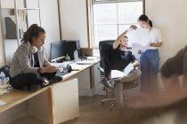 Uomini d'affari creativi discutono di scartoffie in ufficio — Foto stock