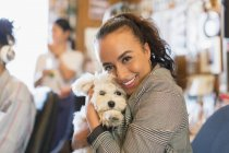 Portrait happy businesswoman with cute dog in office — Stock Photo