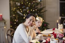 Portrait smiling mother and daughter enjoying candlelight Christmas dinner — Stock Photo