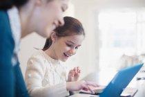 Sorridente ragazza e madre utilizzando il computer portatile — Foto stock