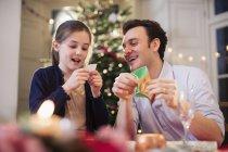 Отец и дочь открывают рождественский крекер на рождественском ужине — стоковое фото
