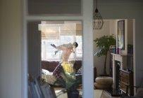 Pai levantando filho na sala de estar sofá — Fotografia de Stock