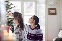 Мать и дочь украшают елку — стоковое фото
