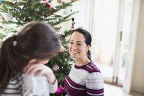 Улыбающиеся мать и дочь разговаривают за елкой — стоковое фото