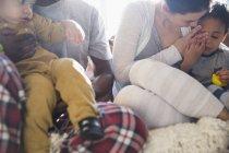 Giovane famiglia in pigiama rilassante sul divano — Foto stock