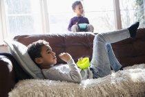 Brüder entspannen, fernsehen und Snacks auf dem Wohnzimmersofa genießen — Stockfoto