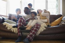 Young family relaxing in pajamas on living room sofa — Stock Photo
