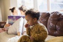 Innocent baby boy sucking thumb on sofa — Stock Photo