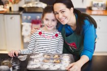 Portrait smiling mother and daughter baking in kitchen — Stock Photo