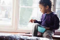 Niedlicher, unschuldiger Junge beim Zählen von Snacks auf der Fensterbank — Stockfoto