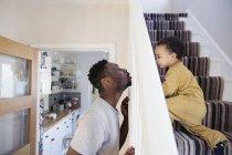 Brincalhão pai e filho criança rastejando escadas acima — Fotografia de Stock