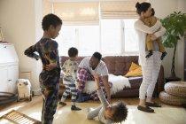 Multi-ethnic young family in pajamas playing and relaxing in living room — Stock Photo
