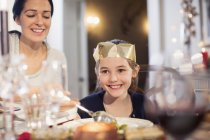 Smiling mother and daughter in paper crown enjoying Christmas dinner — Stock Photo