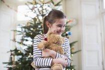 Glückliches Mädchen umarmt Teddybär vor dem Weihnachtsbaum — Stockfoto